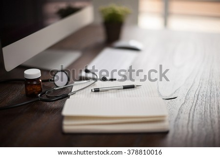 Closeup of the workplace of a doctor with a stethoscope and a notepad with shallow depth of field - stock photo