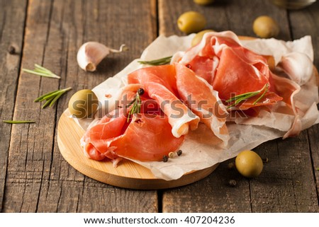 closeup of thin slices of prosciutto with mixed olives and paprika on wooden cutting board - stock photo