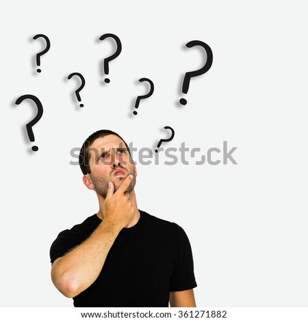 closeup of thoughtful young caucasian man with black tshirt isolated on white background surrounded by question marks