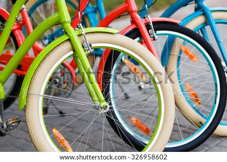 Closeup of three bright colored city urban woman bikes tires row outdoors in the park - stock photo