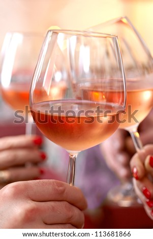 Closeup of three chilled glasses of wine clinking together in a celebratory toast - stock photo
