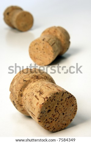 closeup of three corks over light background from above - stock photo