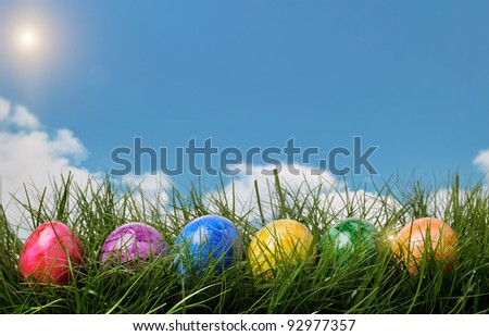 Closeup of three dyed Easter Eggs in the grass with a blue cloudy sky background