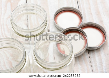 Closeup of three glass canning jars on a rustic wood farmhouse style kitchen table. The lids are laying in the background. Shallow depth of field with focus on the jar rims. - stock photo
