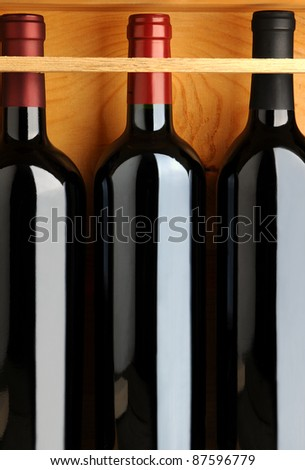Closeup of three red wine bottles in a wooden case. Vertical format.