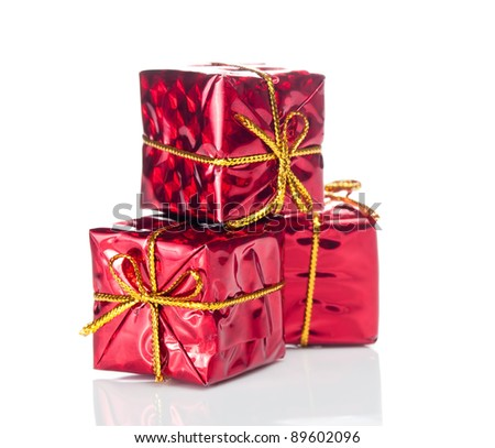 Closeup of three small red gift boxes with gold tapes on white - stock photo