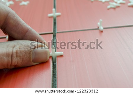 Closeup of tilers hand while using spacer for installing a red ceramic tiles on the floor. - stock photo