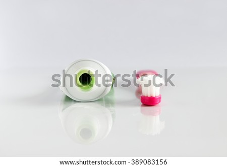 Closeup of toothpaste tube and used toothbrush on white. - stock photo