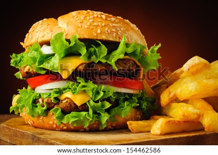 closeup of traditional cheeseburger or hamburger and french fries - stock photo