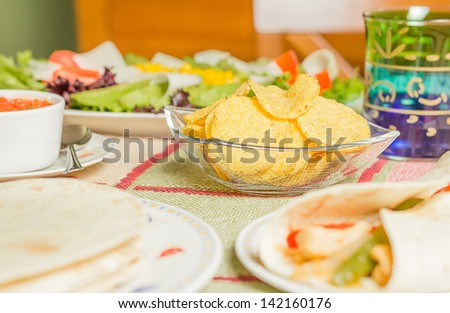 Closeup of traditional mexican food in a table, with  a bowl of nachos, spicy sauce, a plate of chicken fajita, tortillas and fresh salad - stock photo
