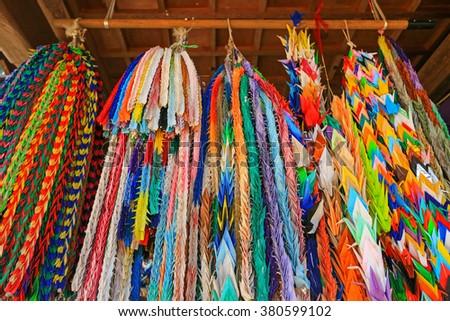 Closeup of traditional thousand Origami cranes, long prayer strings hanging at Hokkeji Temple in Takayama, Gifu, Japan - stock photo