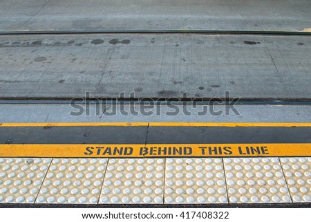 Closeup of tramway with yellow signage ?STAND BEHIND THIS LINE? on concrete road at the tram stop in Melbourne, Australia  - stock photo