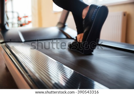 Closeup of treadmill used by sportswoman in black sneakers for running in gym - stock photo