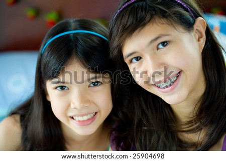 Closeup of two beautiful sisters in home environment