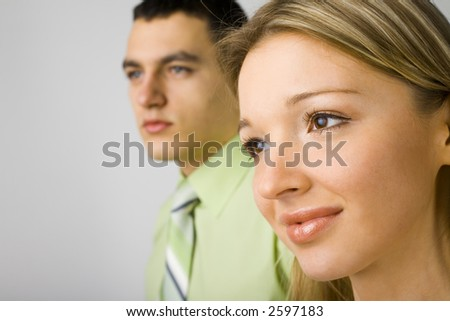 Closeup of two business people's faces. Woman is on the front. Focus on her face. They're looking forward.