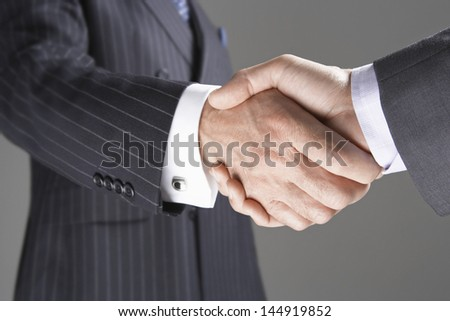 Closeup of two businessmen shaking hands against gray background - stock photo