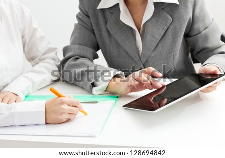 Closeup of two businesswomen around the table at work.	 - stock photo