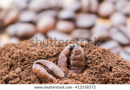 Closeup of two coffee beans at roasted coffee heap. Coffee bean on macro ground coffee background.  - ingredient of hot beverage. - stock photo
