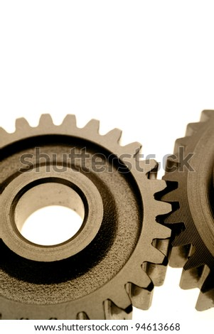 Closeup of two cogs on plain background - stock photo