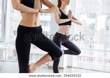 Closeup of two concentrated young women standing and doing balancing pose in yoga studio - stock photo