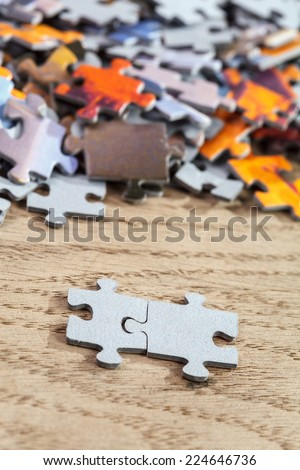 Closeup of two connected jigsaw puzzle pieces on a table. Shallow depth of field - stock photo