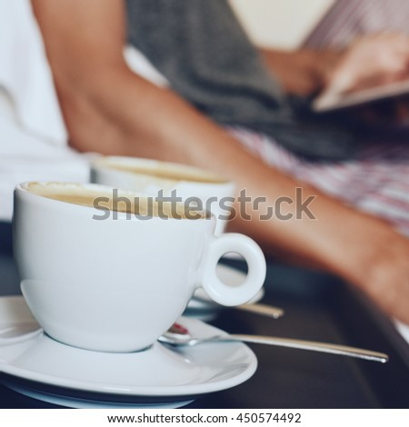 closeup of two cups of coffee in the foreground and a young caucasian man in pajamas in bed using a tablet computer in the background