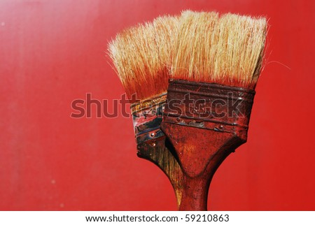 closeup of two dirty paintbrushes against red background - stock photo
