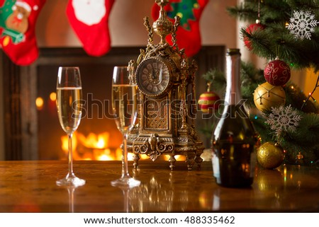 Closeup of two glasses of champagne on table next to old clock showing midnight at living room decorated for Christmas. Concept of waiting for New Year