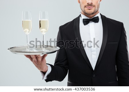 Closeup of two glasses of champagne on tray holded by handsome waiter in tuxedo over white background