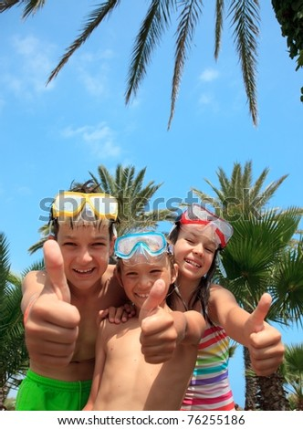 Closeup of two happy brothers and sister in snorkel masks gesturing with thumbs up, tropical palm trees in background.