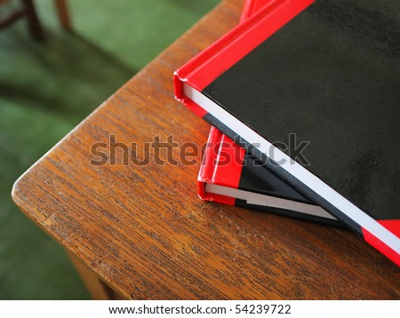 Closeup of two notebooks placed at the corner of a desk in classroom of high school - stock photo