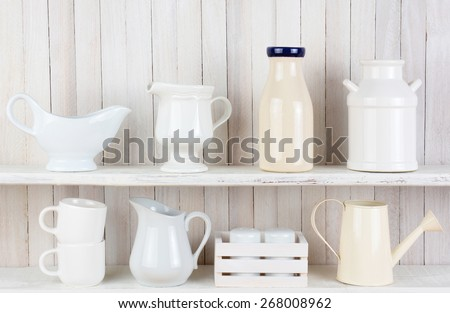Closeup of two white wood rustic kitchen shelves with assorted household items. Various objects, include, salt and pepper shakers, cups, pitchers bottles and crockery. - stock photo