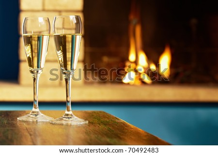 closeup of two wine glasses with champagne on table and fireplace in background. Horizontal shape - stock photo