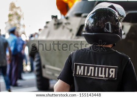 closeup of ukrainian riot policeman wearing protective vest and helmet with armored military vehicle in background.