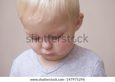 Closeup of unhappy baby boy on colored background - stock photo