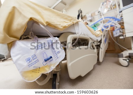Closeup of urine bag attached to bed in hospital - stock photo