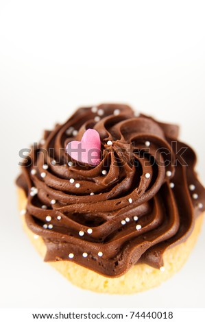 Closeup of  Vanilla Cupcake with Heart Candy and Pink Sprinkles