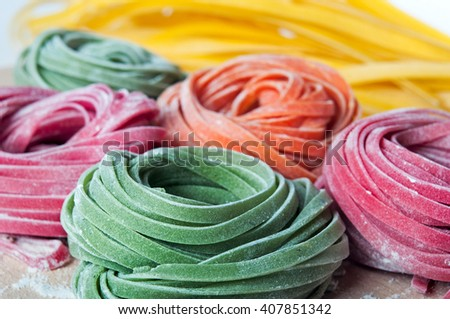 Closeup of varicolored raw italian pasta with natural vegetable dyes (spinach, paprika, beet); shot in shallow depth of field - stock photo