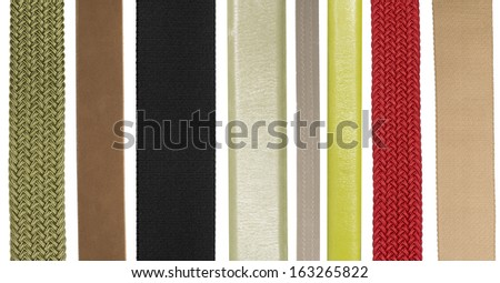 Closeup of various leather and fabric belts isolated on white background - stock photo