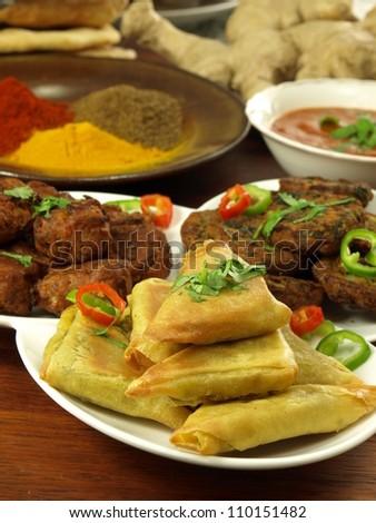 Closeup of vegetarian samosas with bhajis and pakoras - stock photo