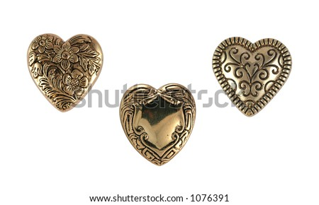 Closeup of vintage brass heart buttons on white background. - stock photo
