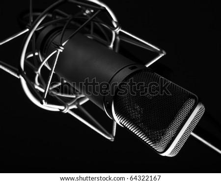 closeup of vintage memebrane microphone on black background - stock photo