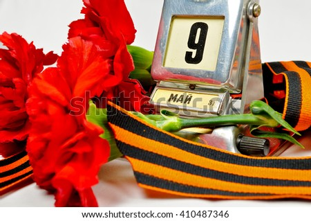 Closeup of vintage metal desk calendar with 9 May date and George ribbon and red carnations -  Victory Day 9 May concept.  - stock photo