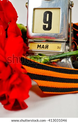 Closeup of vintage metal desk calendar with 9th May date and George ribbon and red carnations -  Victory Day 9 May concept.  - stock photo
