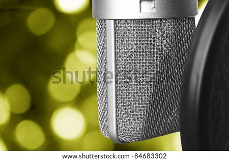 closeup of vintage microphone against abstract yellow lights - stock photo