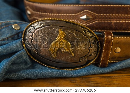 Closeup of Vintage silver buckle with cowboy on bucking bronc.  Leather belt with studs against blue denim button-snap work shirt background. - stock photo