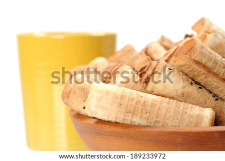 closeup of waffle rolls and cup of tea isolated on white