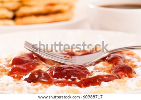 Closeup of waffle with strawberry jam, powdered sugar and fork. Coffee and waffles in background - stock photo