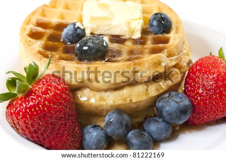 Closeup of waffles, strawberries, blueberries, and butter.   Isolated on white background. - stock photo