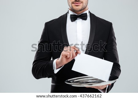 Closeup of waiter in tuxedo with bowtie holding blank card on tray - stock photo